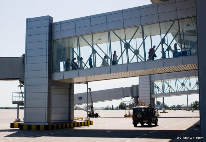 Пассажиры следуют из самолета в терминал по телетрапу