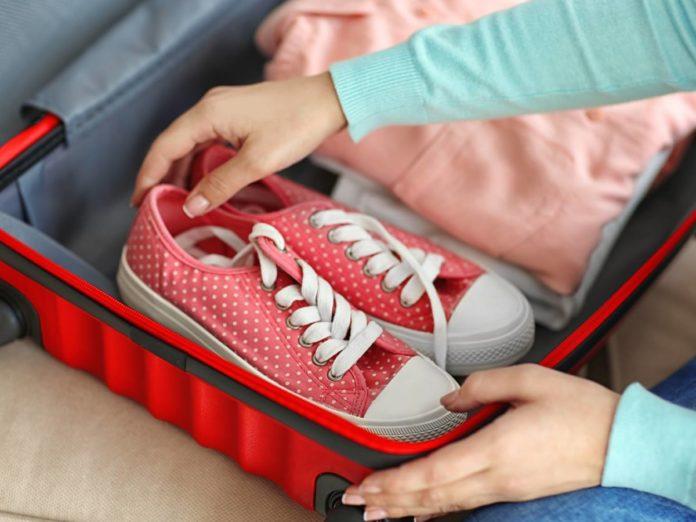 Упаковка вещей в чемодан, который будет перевозиться в ручной клади
