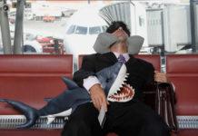 Пассажир, спящий в аэропорту в ожидании рейса