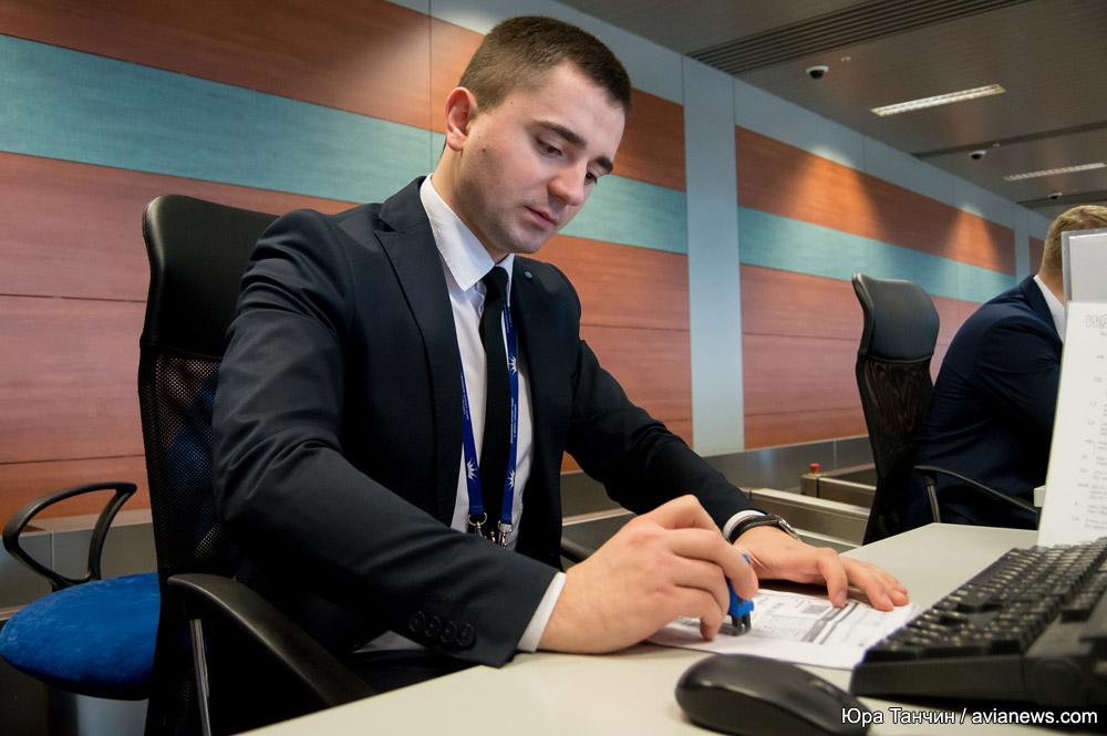 Сотрудник службы организации перевозок в аэропорту Львов ставит печать о проверке документов пассажира на посадочный талон
