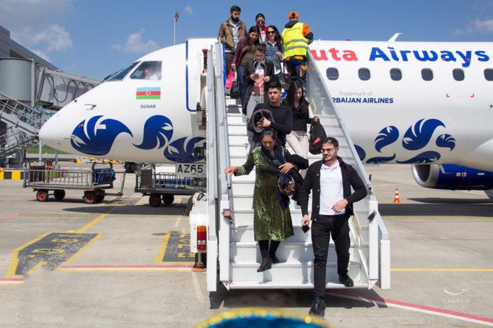 Пассажиры выходят из самолета Buta Airways в аэропорту Харькова
