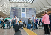 Пассажир смотрит на табло вылетов в аэропорту