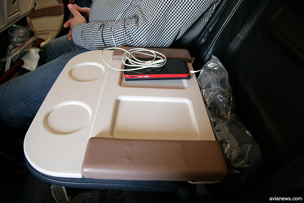 Среднее кресло, разложенное в столик для напитков в бизнес-классе