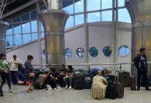 Пассажиры ожидают начала регистрации в аэропорту Алматы, сидя на чемоданах
