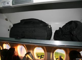 Ручная кладь на багажной полке в салоне самолета