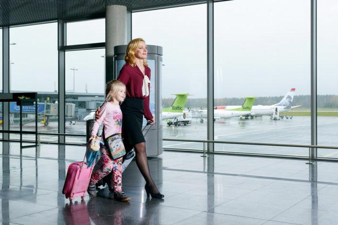 Взрослый сопровождает ребенка к выходу на посадку в самолет в аэропорту Рига