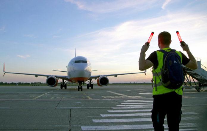Самолет заруливает на стоянку в аэропорту с помощью команд маршала