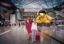 Сотрудник Qatar Airways сопровождает ребенка в аэропорту Дохи