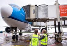Автоматический сдвоенный телетрап присоединен к Boeing 777 KLM в аэропорту Амстердама Схипхол