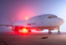 Самолет SkyUp на стоянке в аэропорту в сильный туман