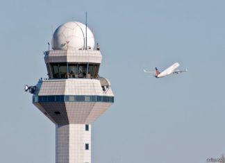 Диспетчерская вышка на фоне взлетающего самолета
