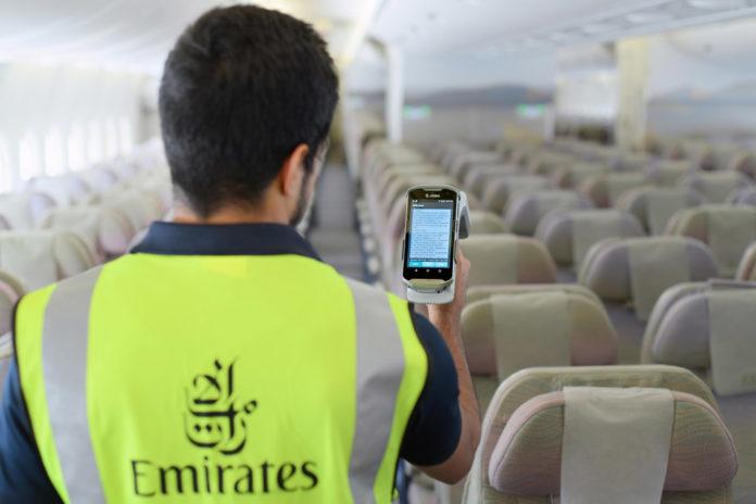 Техник Emirates с помощью сканера проводит считывание информации с RFID-тегов, размещенных на спасательных жилетах в самолете