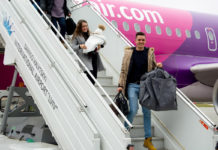 Родители выходят из самолета Wizz Air с 2-миллионным пассажиром аэропорта Львов в 2019 году