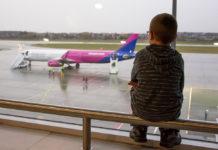 Ребенок в аэропорту наблюдает за самолетом Wizz Air