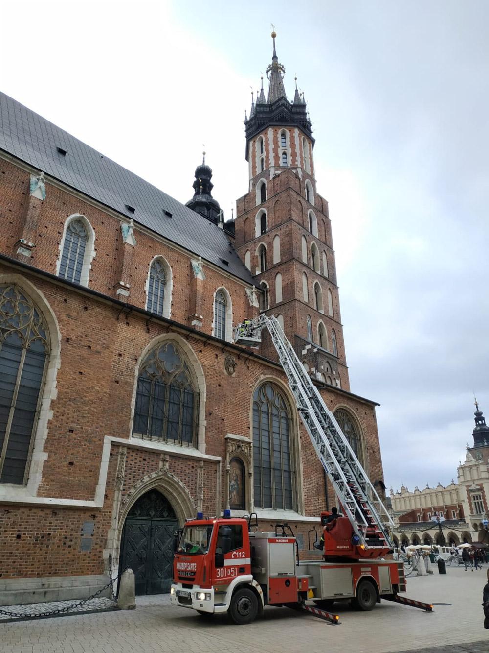 Пожарные достают дрон Mavic Mini с крыши костела Святой Марии в Кракове