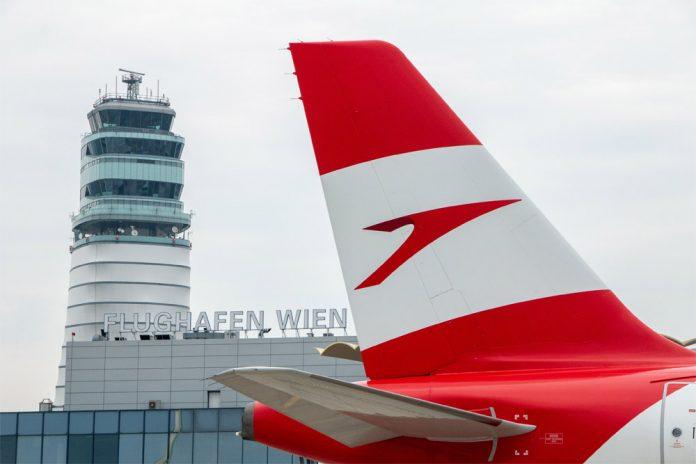 Самолет Austrian Airlines на фоне диспетчерской вышки в аэропорту Вена