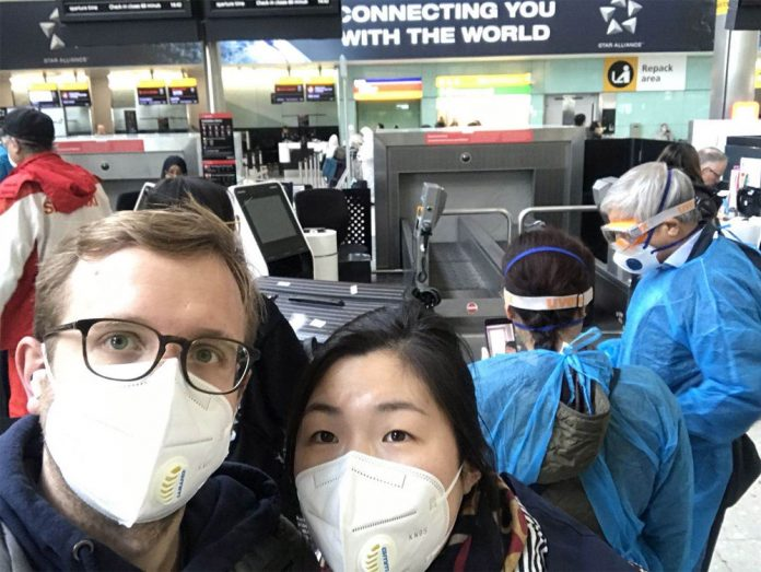 Лукас Хензель и его девушка в защитных масках перед вылетом из Лондона в Пекин