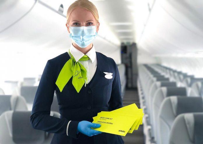 Бортпроводник airBaltic с защитным набором для пассажиров, который включает маску и дезинфицирующую салфетку