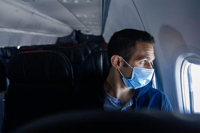Пассажир в маске на борту самолета