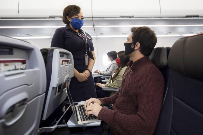 Бортпроводник и пассажиры на борту самолета в масках