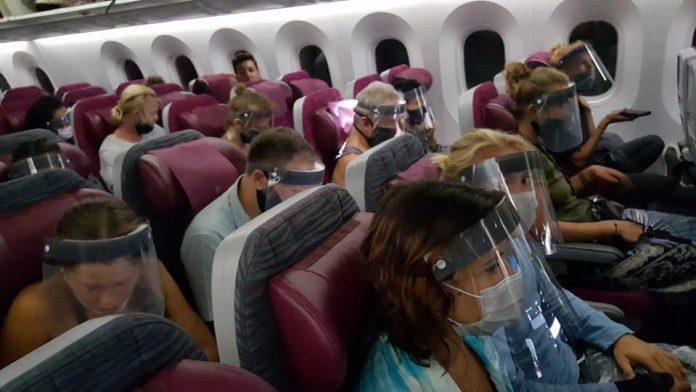 Пассажиры Qatar Airways в защитных экранах и масках на борту самолета