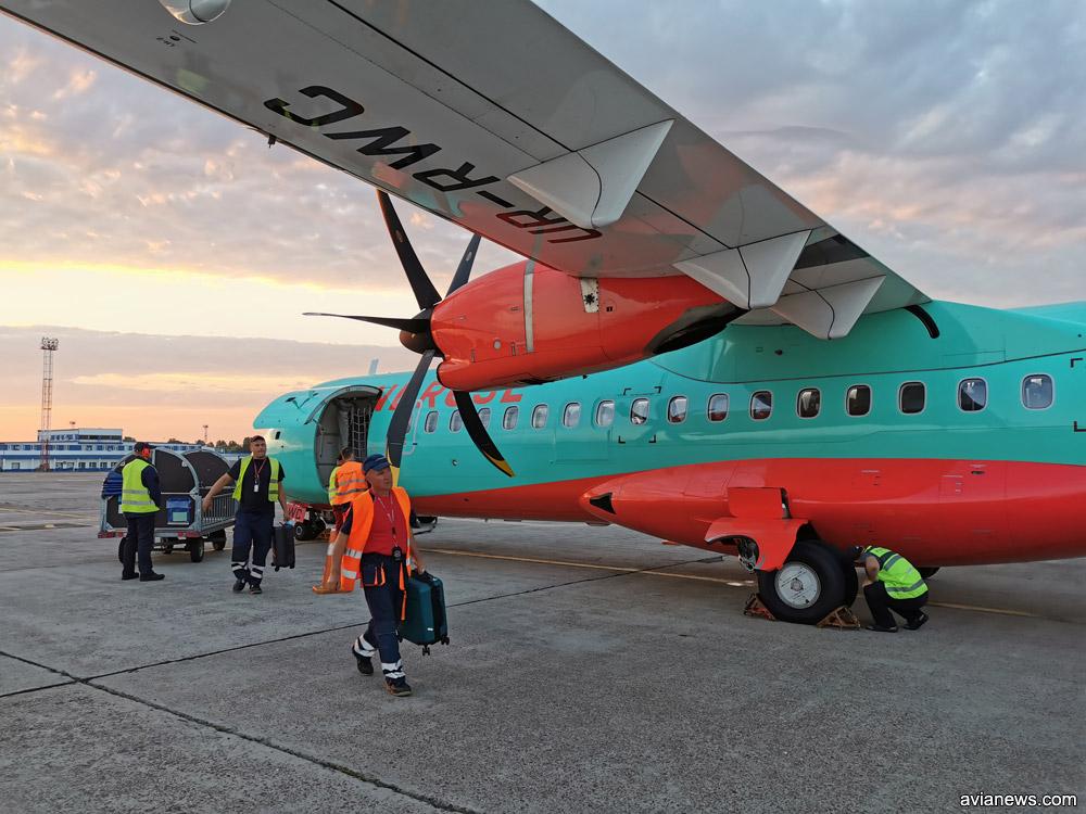 Выгрузка большой ручной клади из ATR 72-600 в аэропорту. Передается пассажирам у трапа самолета по прилету