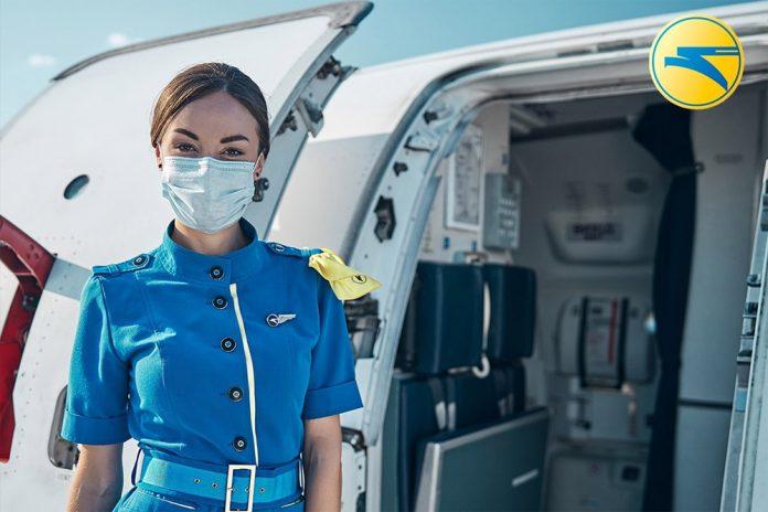 Бортпроводник МАУ в маске у входа в самолет