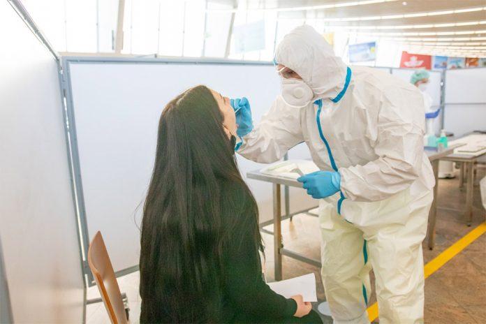 Медицинский работник берет мазок у пассажира для тестирования на коронавирус в аэропорту Вены Швехат