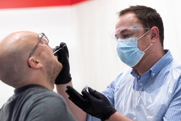 Медик берет анализ на коронавирус у пассажира в аэропорту Хитроу