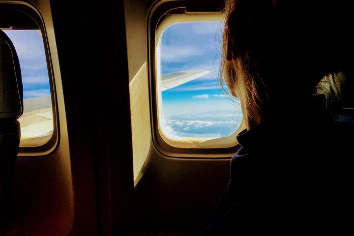 Пассажир в самолете смотрит в окно