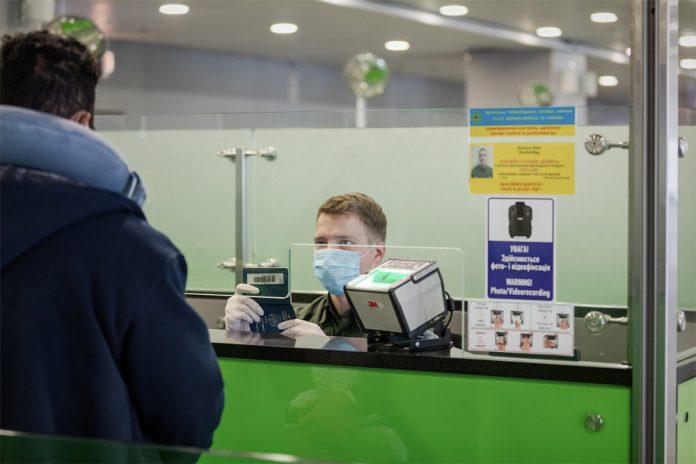 Пограничник в маске проверяет паспорт пассажира