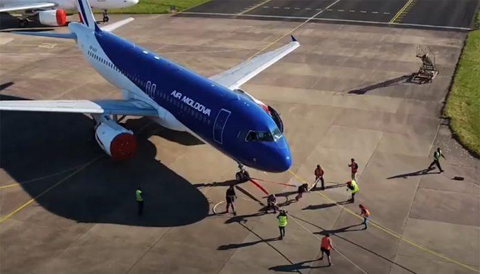 Процесс буксировки самолета Airbus A320 командой из двух женщин