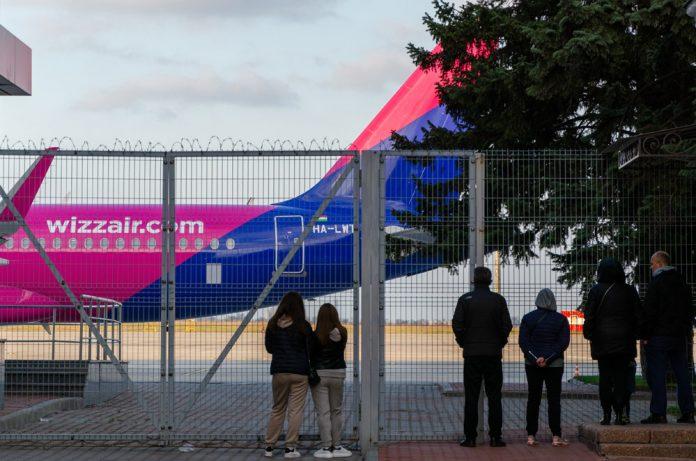 Люди наблюдают за самолетом Wizz Air через забор