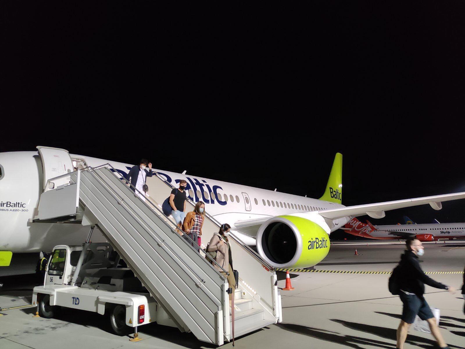 Пассажиры выходят из самолета Airbus A220-300 airBaltic, который прилетел из Риги