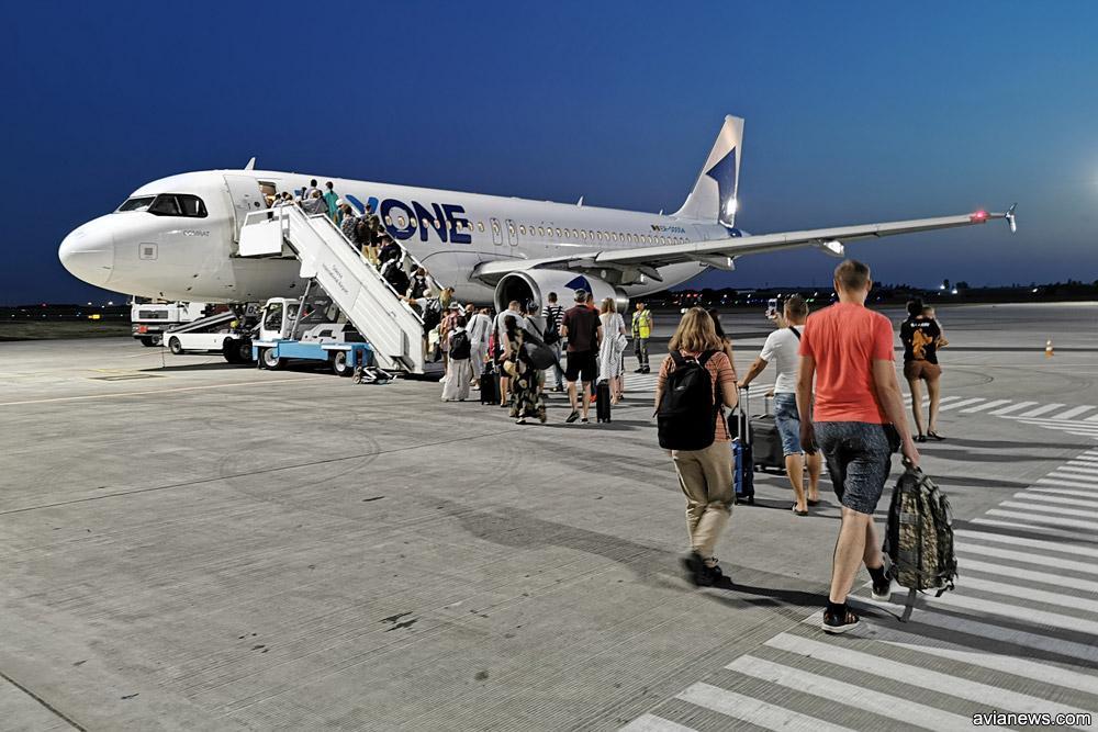 Пассажиры пешком идут от терминала к самолету