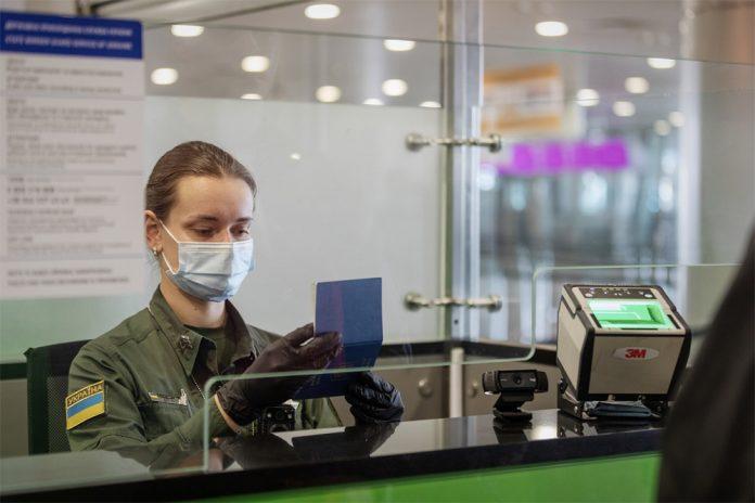 Пограничник на границе Украины проверяет паспорт пассажира