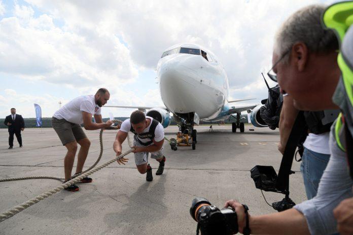 Силач Иннокентий Веселов перетягивает самолет Boeing 737-800 авиакомпании Nordstar в аэропорту Красноярска