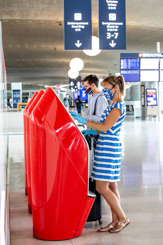 Пассажиры у киосков самостоятельной регистрации в аэропорту Парижа