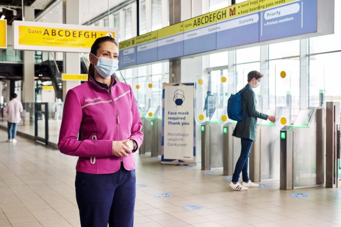 Пассажиры и работники аэропорта Схипхол в масках
