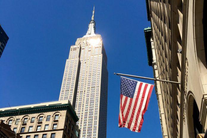 Флаг США на фоне небоскреба в Нью-Йорке